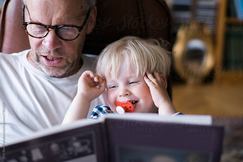 Toddler enjoying time with grandpa reading a book by Per Swantesson for Stocksy United