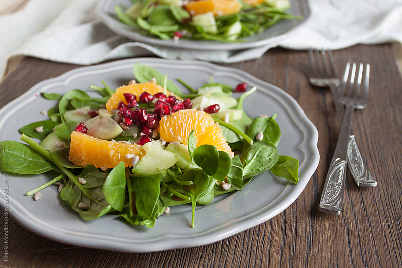 Fresh spinach salad with orange, cucumber and pomegranate seeds by Nataša Mandić for Stocksy United
