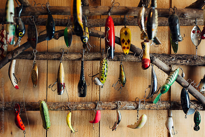 Various fishing tackles on a rack at a cabin by Gabriel (Gabi) Bucataru for Stocksy United