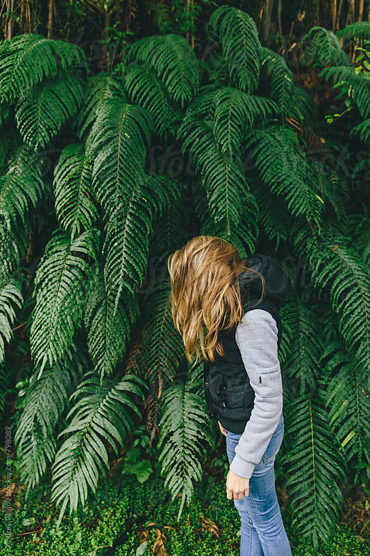 Girl fooling around near a fern by Andrey Pavlov for Stocksy United