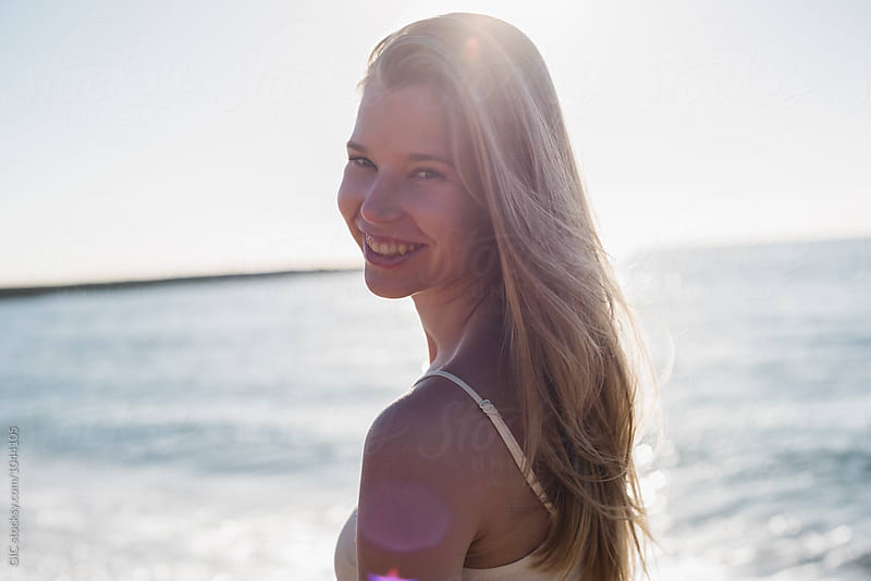 Happy smiling young blonde portrait in front of the sea by Simone Becchetti for Stocksy United