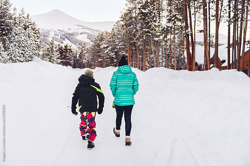 Brother and sister walk a snow covered road in winter by Angela Lumsden for Stocksy United