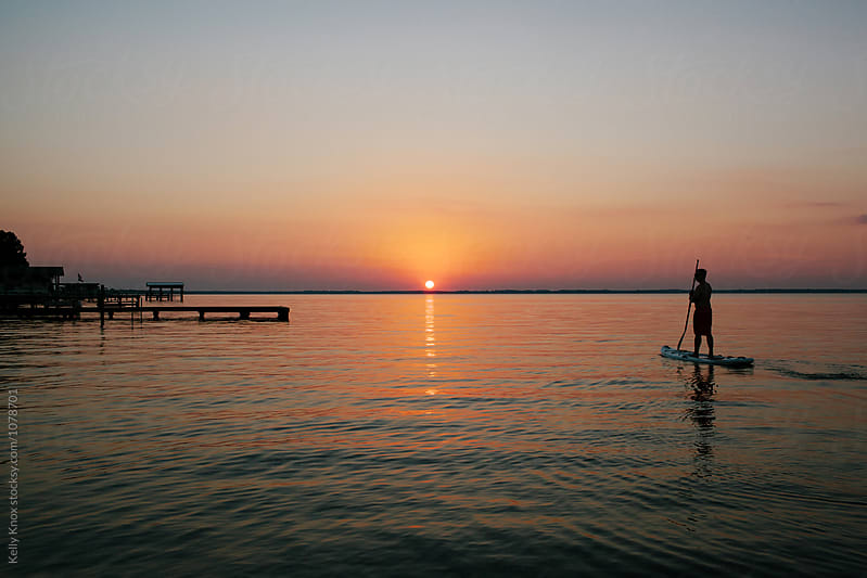 man on a paddle board watches the sunset by Kelly Knox for Stocksy United