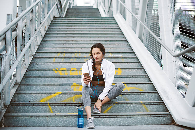 Young woman sitting on city staircase after workout. by Kate Daigneault for Stocksy United