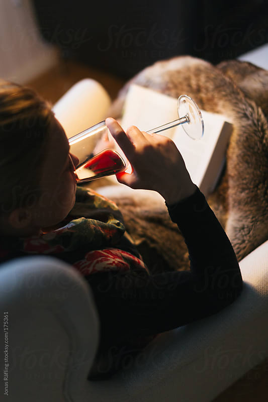 Women sipping on a glass of wine and reading a good book by Jonas Räfling for Stocksy United