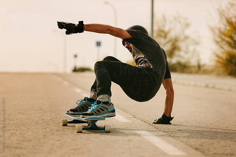Young Man Longboarding in the Street by VICTOR TORRES for Stocksy United
