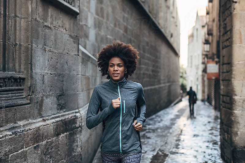 Young african american woman running on Barcelona streets.  by BONNINSTUDIO for Stocksy United