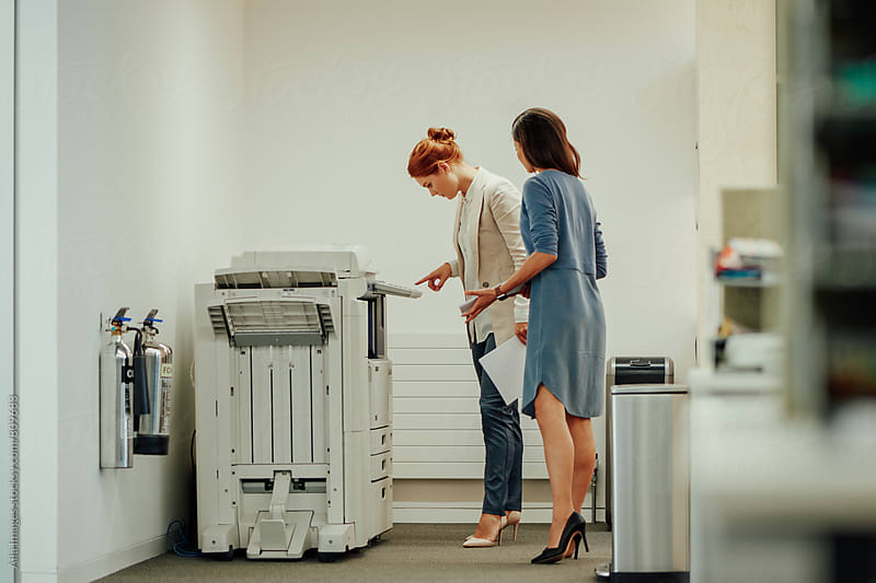 Young businesswomen figuring out how to use photostat machine by Aila Images for Stocksy United