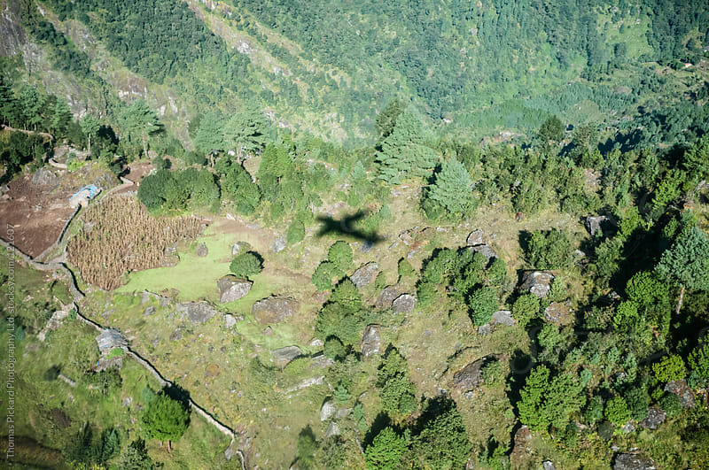 Shadow of a plane on the foothills immediately below Lukla Airport, Everest Region, Nepal. by Thomas Pickard for Stocksy United
