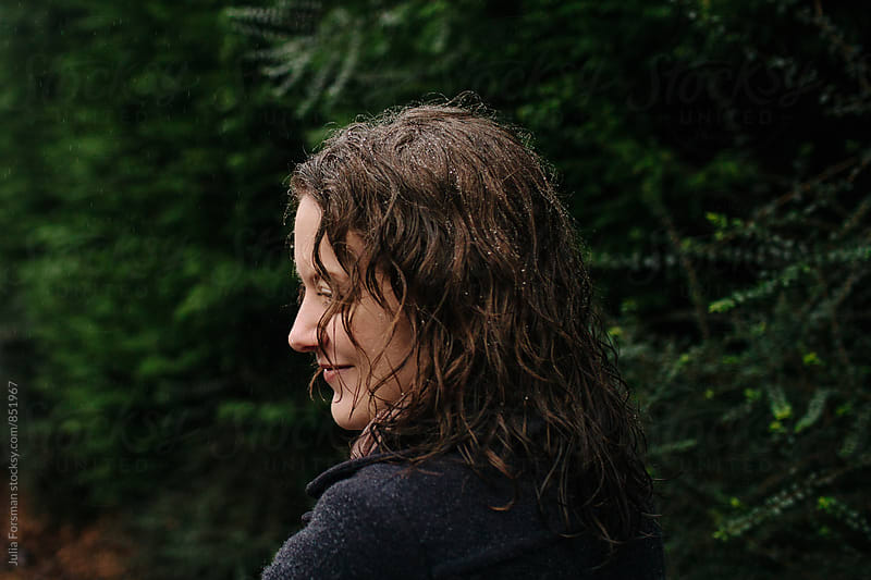 Woman smiling as she walks in the rain. by Julia Forsman for Stocksy United
