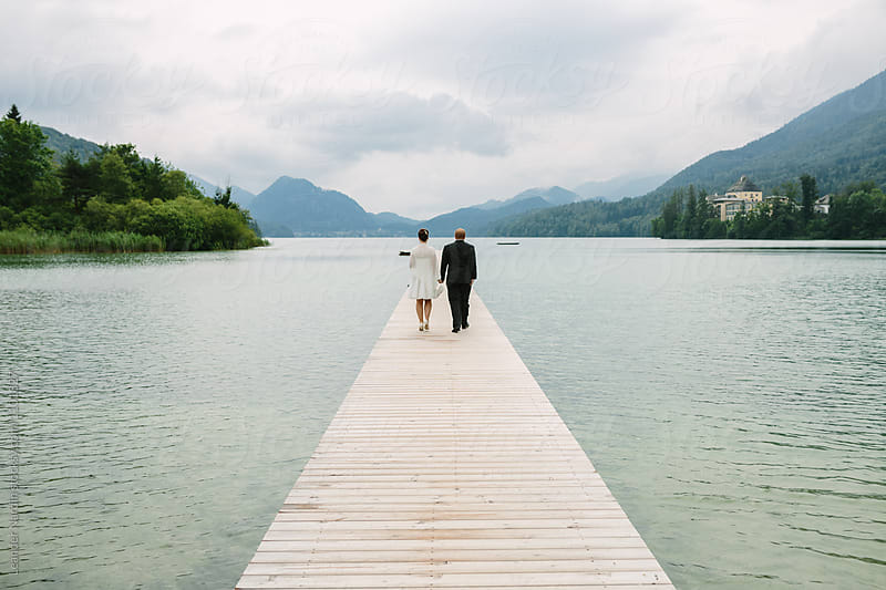 bridal couple walking on a jetty at a lake by Leander Nardin for Stocksy United
