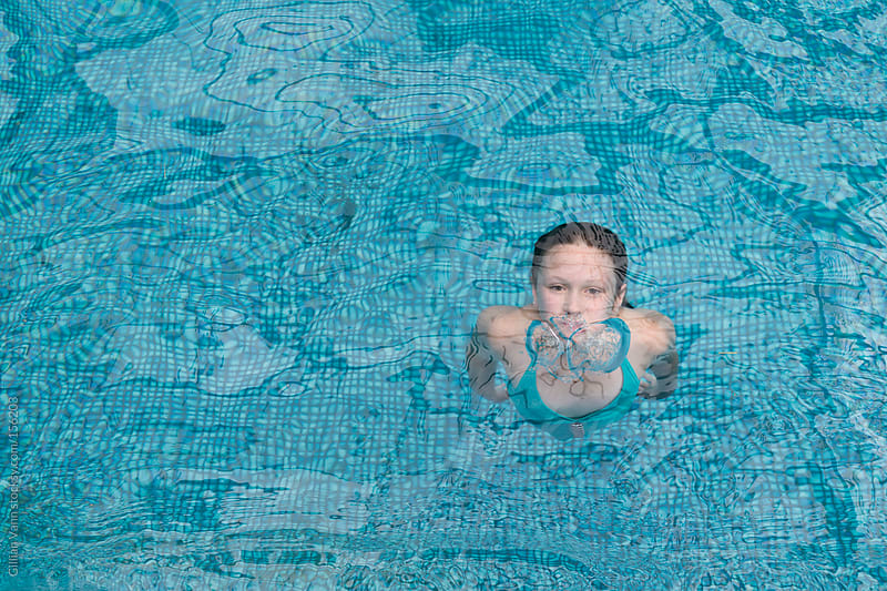 girl surfacing in pool by Gillian Vann for Stocksy United