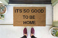 "Woman standing in front of a doormat reading ""It's so good to be home"" by Amy Covington for Stocksy United"