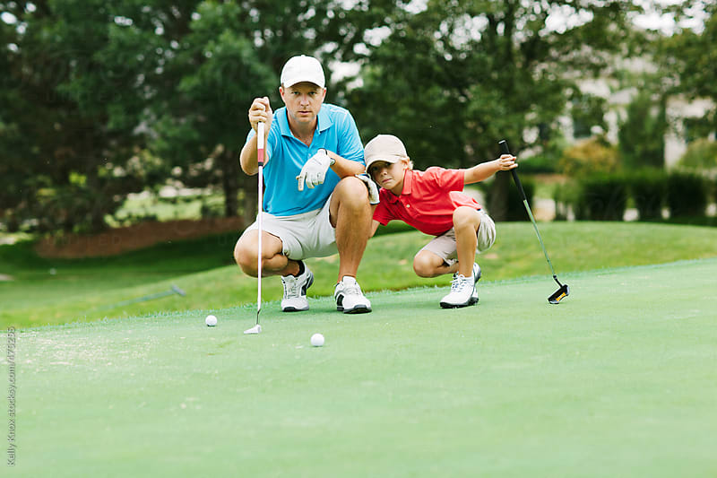 father teaching his son how to line up a putt  by Kelly Knox for Stocksy United