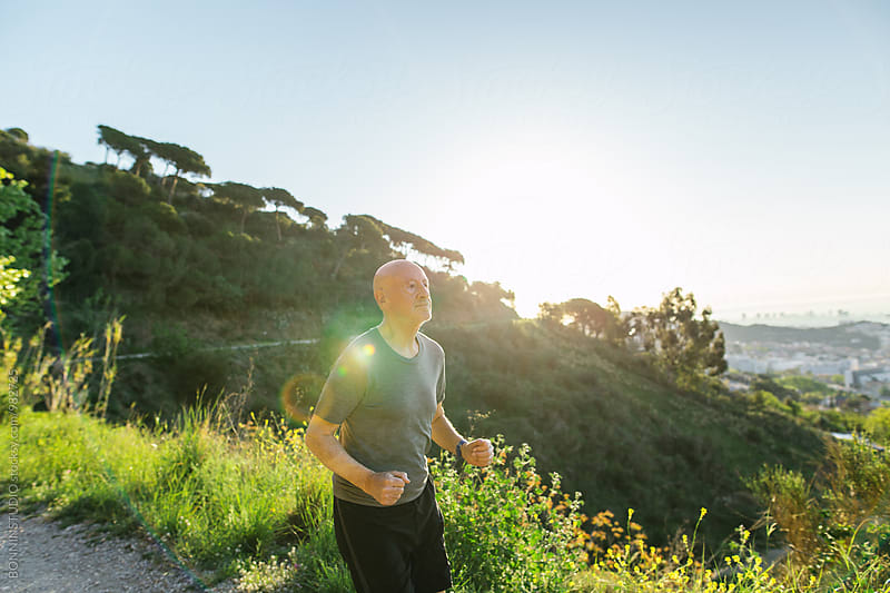 Senior man running in the mountain at morning.  by BONNINSTUDIO for Stocksy United
