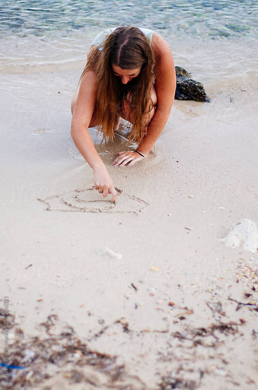 Young woman drawing in the sand by Boris Jovanovic for Stocksy United