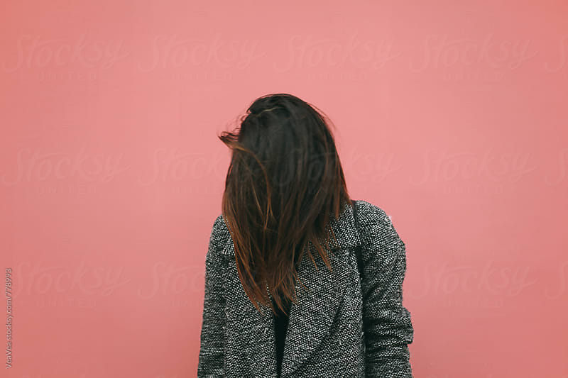 Brunette woman standing in front of a pink wall by VeaVea for Stocksy United