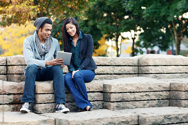 Two people using tablet in city park by Isaac Lane Koval for Stocksy United