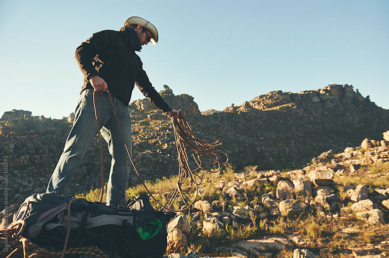 man throws rope by Daxiao Productions for Stocksy United