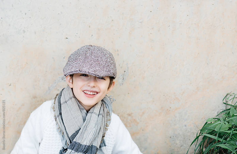 Boy laughing at camera with his cap almost covering his eyes by Beatrix Boros for Stocksy United