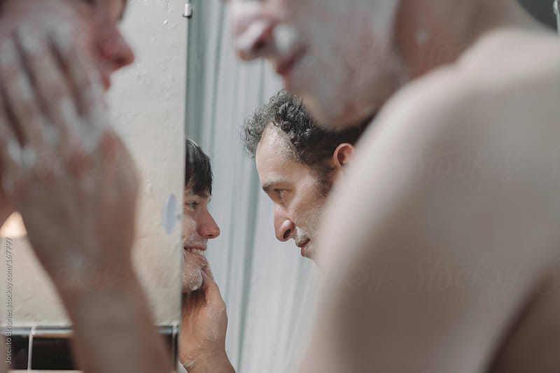 Gay couple shaving together, sharing a bathroom in the morning by Joselito Briones for Stocksy United
