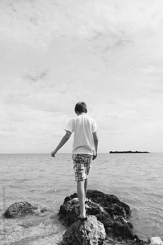 Boy standing on a rock by the ocean by Stephen Morris for Stocksy United
