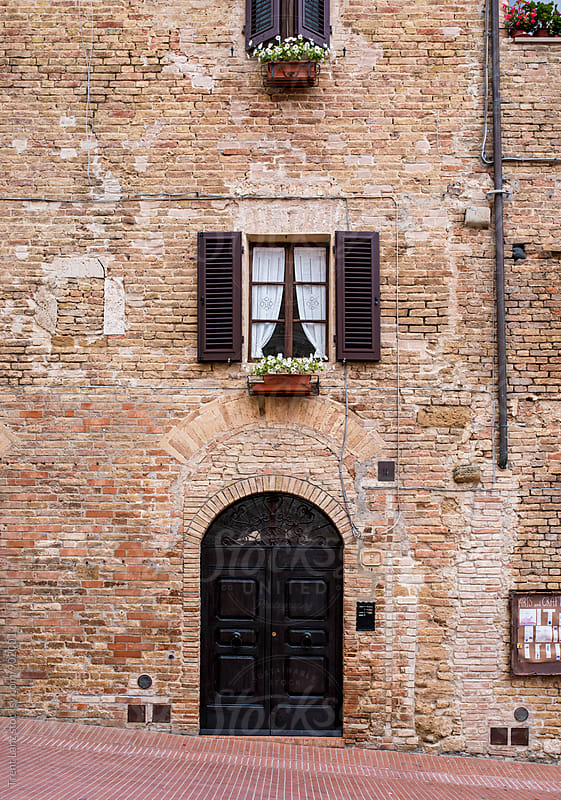 View on brick wall of building with windows and door in San Gimignano, Italy by Trent Lanz for Stocksy United