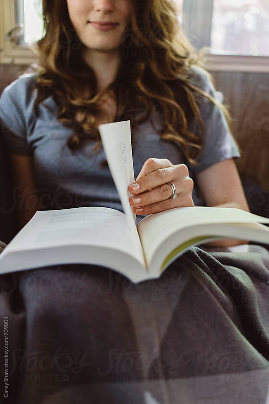 Close up of woman reading a novel by Carey Shaw for Stocksy United