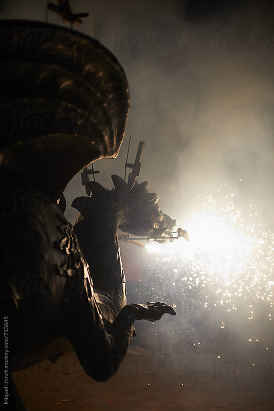 Silhouette of dragon spitting fire in a street parade by Miquel Llonch for Stocksy United
