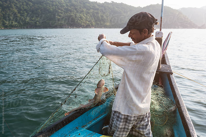 fisherman holding a fish in his net  by RG&B Images for Stocksy United