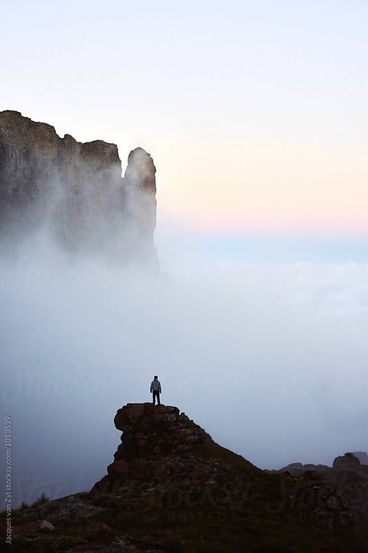 From a precarious and airy rock peak a hiker stands in owe of the majestic misty mountains that surround him.  by Jacques van Zyl for Stocksy United