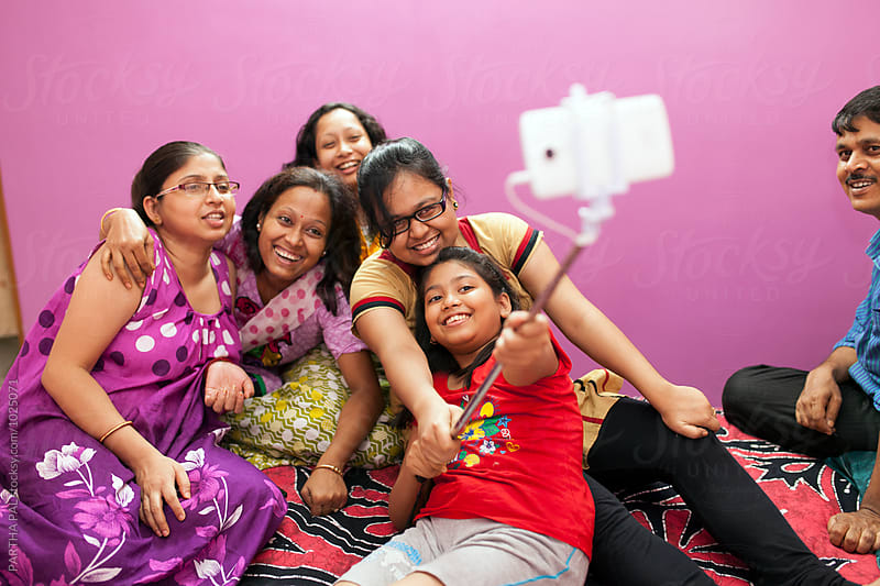 Women and girls taking selfie with selfie stand by PARTHA PAL for Stocksy United