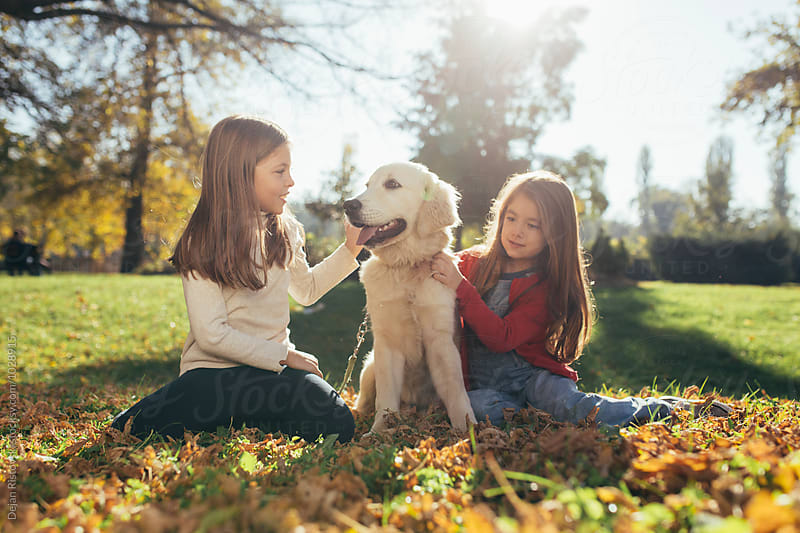 Two girls and a Golden Retriever. by Dejan Ristovski for Stocksy United