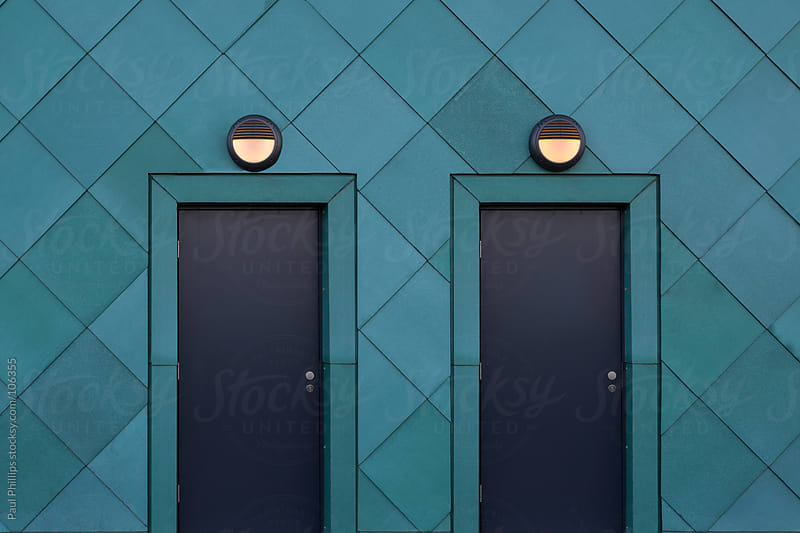 Two matching metal doors with lights above in a green metal-clad building by Paul Phillips for Stocksy United