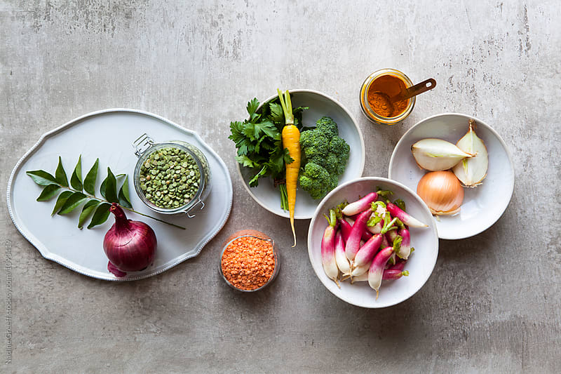 Variety of vegetables, spices and pulses on kitchen table by Nadine Greeff for Stocksy United