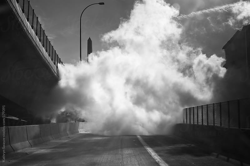 Thick cloud of steam sits on road. by Kathryn Swayze for Stocksy United