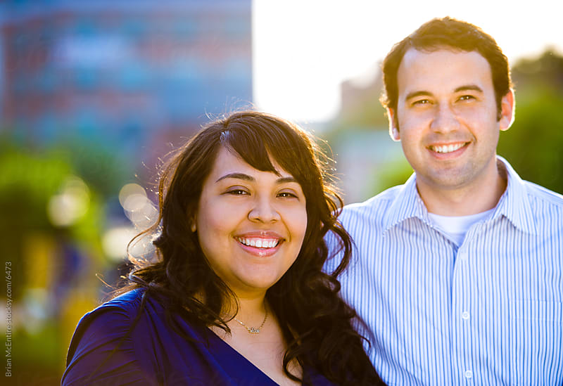 Charming Hispanic Couple in Urban Setting (Strong Backlight) by Brian McEntire for Stocksy United