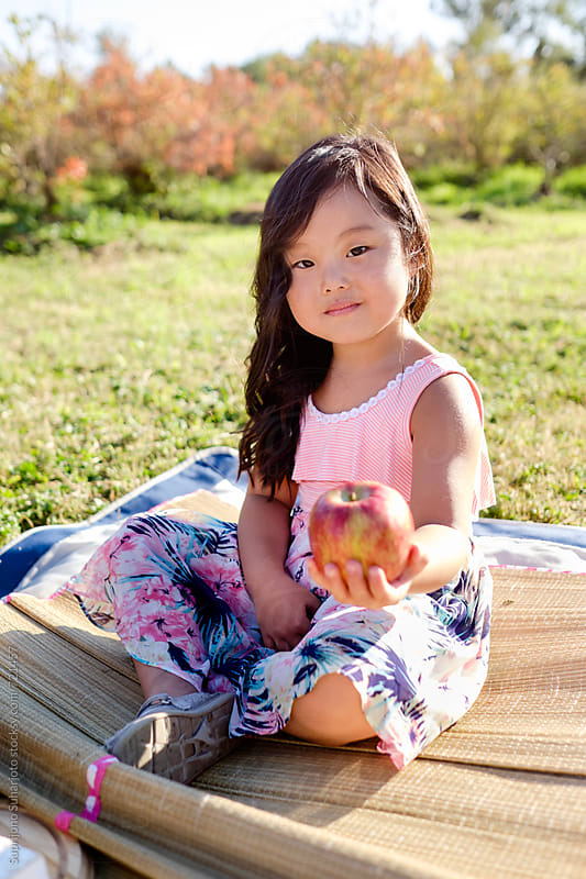 Asian girl holding an apple on a picnic by Suprijono Suharjoto for Stocksy United