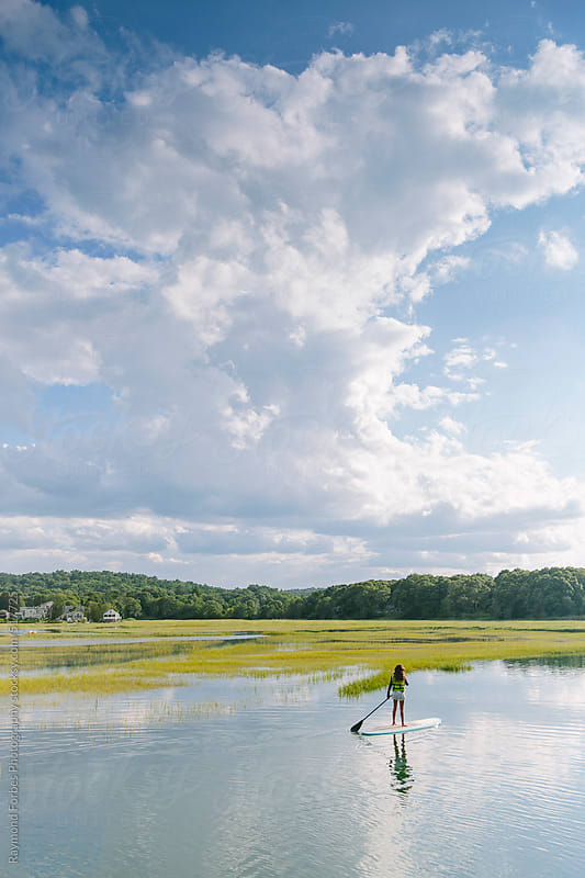 Girl Paddleboarding in Marsh by Raymond Forbes LLC for Stocksy United