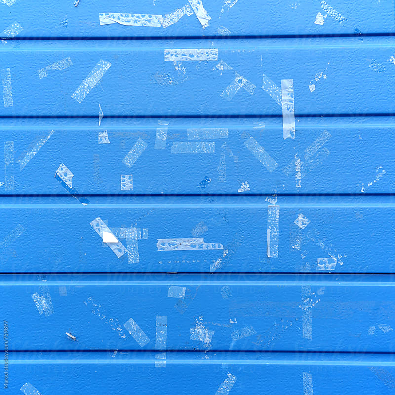 Adhesive tape on a blue door by Marcel for Stocksy United
