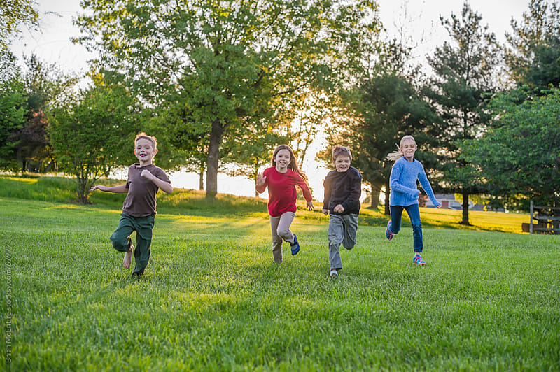 Four Children Running and Playing in Backyard at Sunset by Brian McEntire for Stocksy United