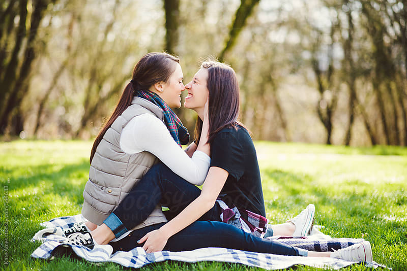 Lesbian couple embracing on a blanket in the park.  by Kate Daigneault for Stocksy United