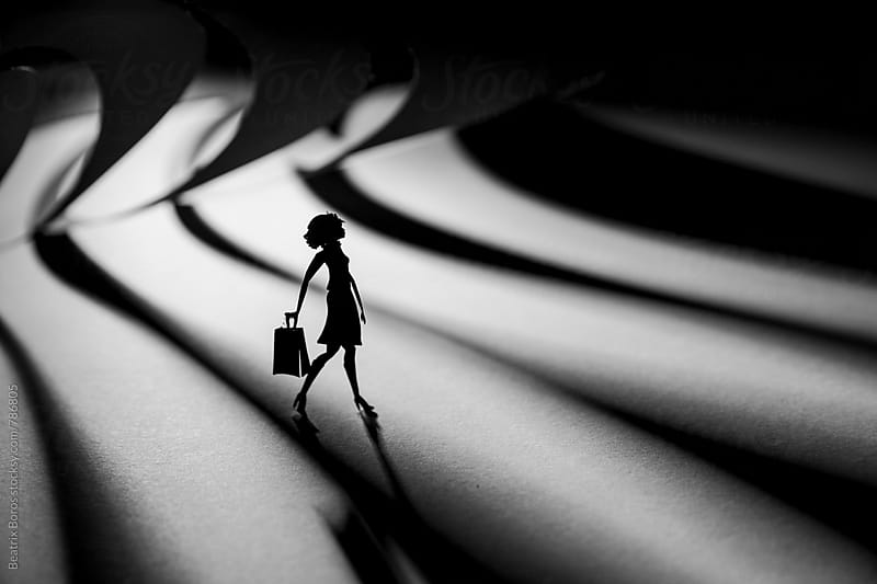 Paper woman walking in a striped ambience with a shopping bag by Beatrix Boros for Stocksy United