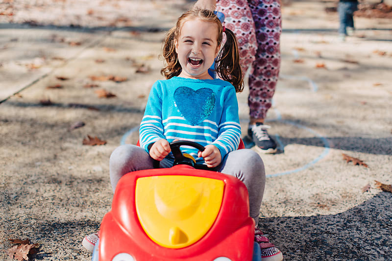 Cute young girls in pigtails riding a toy car by Jakob for Stocksy United