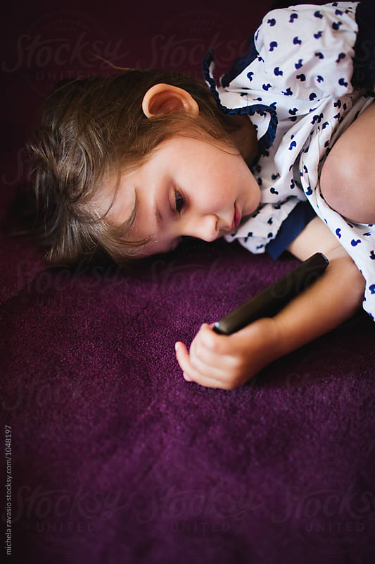 Little girl lying on the carpet holding mobile phone by michela ravasio for Stocksy United