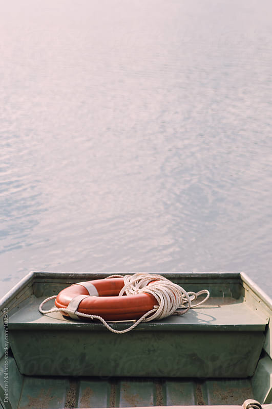 orange life saver on back of rowboat in lake by Deirdre Malfatto for Stocksy United