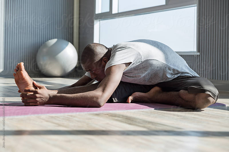 Fit young man bending over and doing a stretch in a yoga practice  by Jovo Jovanovic for Stocksy United