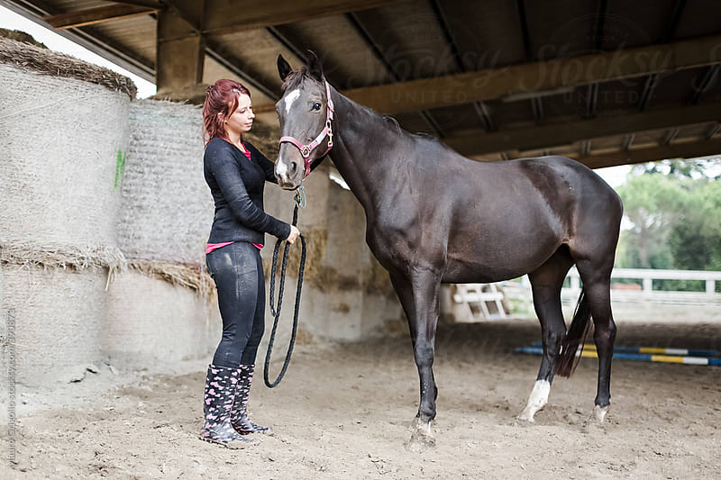 Woman and her horse at the stables by Mauro Grigollo for Stocksy United