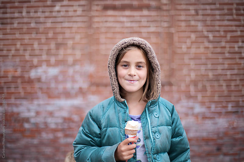 Girl enjoys ice cream in front of bricks by Carleton Photography for Stocksy United