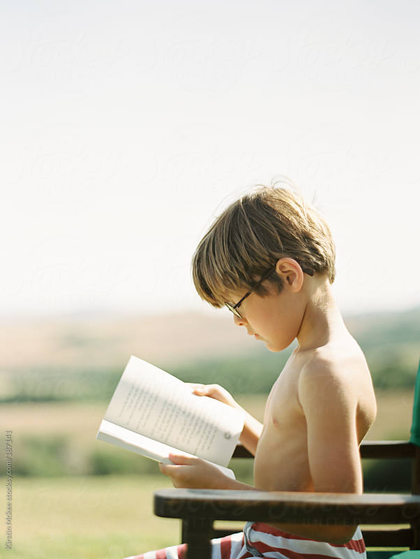 Profile of boy reading book by Kirstin Mckee for Stocksy United